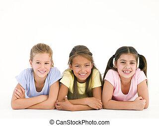fila, tres, amigos, acostado, Abajo, sonriente