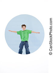 Young boy standing with arms out smiling