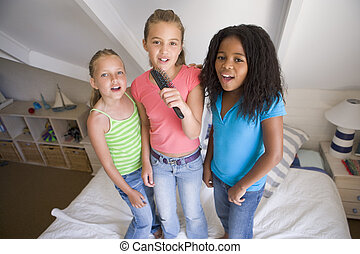 Three Young Girls Standing On A Bed, Singing Into A...
