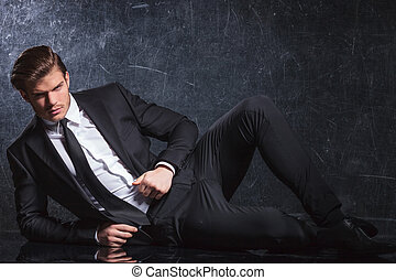 sexy young fashion man lying down in studio and looks at the...