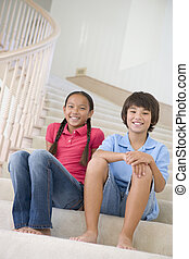 Brother And Sister Sitting On A Stairwell At Home