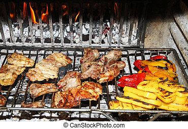 tasty grilled pork and chicken with peppers and grilled vegetables in a large fireplace in the restaurant in Italy