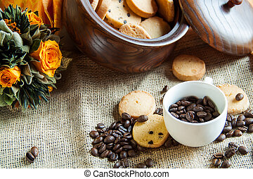 Cup with coffee beans and cookies