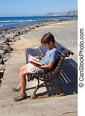 boy reading book - boy reading book on summer bench on sea...