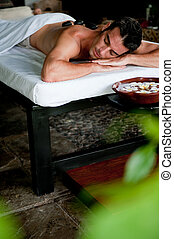 Man at Spa - A good-looking man relaxing with hot stones on...