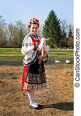 The smiling girl in folk costume with little lamb on family...