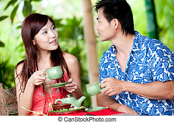 Couple Drinking Tea - A young Chinese couple drinking tea on...