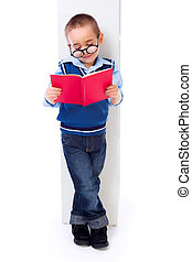 Little boy reading book near shelf