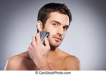 Man shaving. Handsome young man shaving his face with...