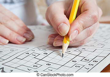 Sudoku - Hand Holding a Pen Playing Sudoku
