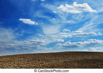 Moody sky - Stunning cloudy background over plowed land...