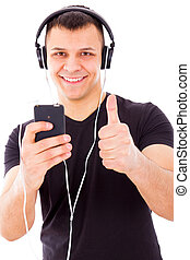 man with headphones listening music on mp3 player holding...