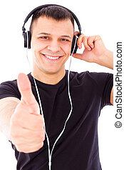 smiling handsome man listening to music showing thumbs up -...