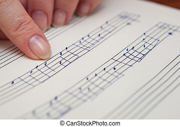 Music book with hand written notes - Finger pointing to...