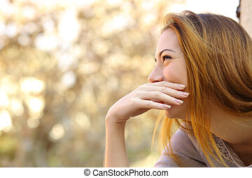Happy woman laughing covering her mouth with a hand with a...