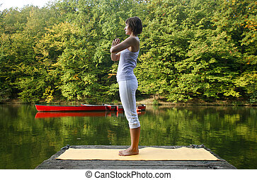 yoga - Woman doing yoga on lake in park in autumn