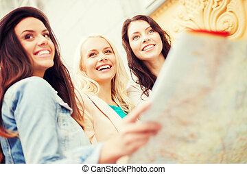 beautiful girls looking into tourist map in city - holidays...