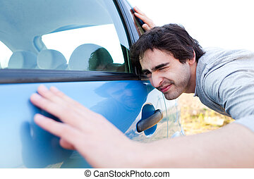 Young man looking for scratches on his car - View of a Young...