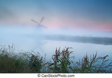 windmill silhouette in dense sunrise fog
