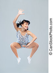Funny girl in pajamas jumping for happiness is studio