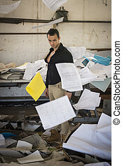 Young man in very messy office with documents flying