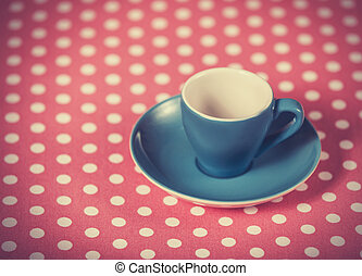 Cup of a coffee on polka dot cover Photo in old color image...