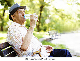 Senior man relaxing outdoors on a park early in the morning....