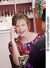 Appalled woman in coffee house with male friend