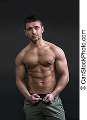 Muscular young man semi naked looking at camera, on dark...