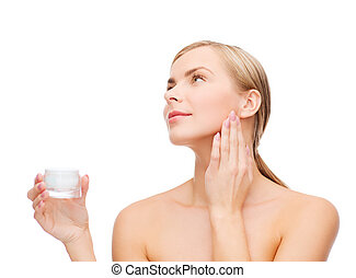 woman applying cream on her skin - cosmetics, health and...