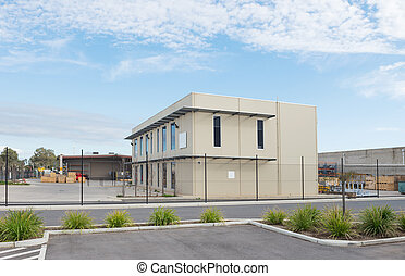 Modern office building with industrial warehouse and...