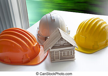 model of wood house on architect working table and safety helmet use for construction home and residence ,civil engineering and architecture topic