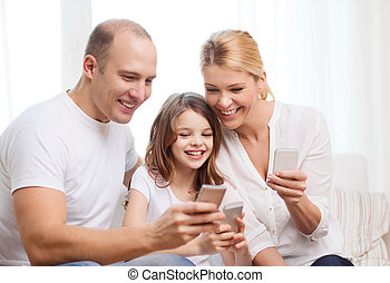 parents and little girl with smartphones at home - family,...