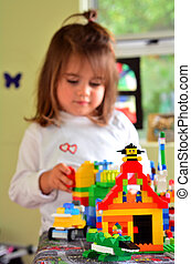 Child play with Lego construction toy