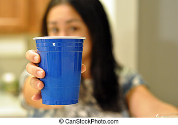 Blue plastic party cup offered by a young woman