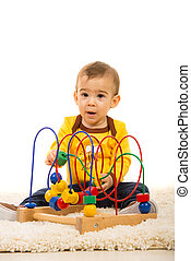 Amazed toddler with wooden toy