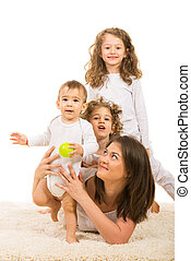 Cheerful family of mother and three kids lying on carpet...