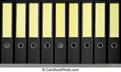 Row of black archive folders on a bookshelf