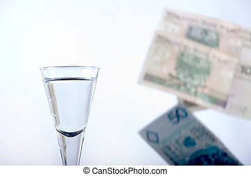 Vodka and falling money - Closeup of a glass of vodka, and...