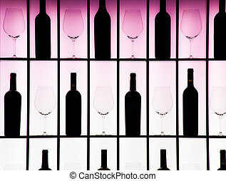 Black bottles and crystal glasses decorate a wall creating a...