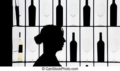 Silouette of a waitress against bottle and glasses