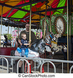 Father and Son on Merry-go-round - Father and Son riding on...