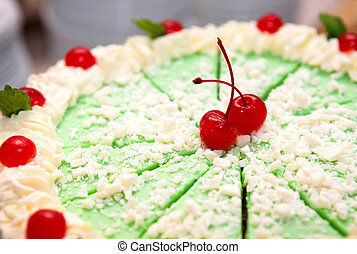 Green Iced Cake With Cherries - A closeup of a lime green...