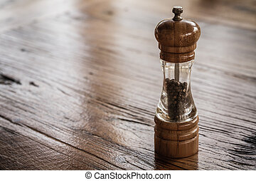 Pepper Mill on Wooden Background - View of a pepper mill on...