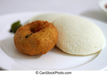 Idli Vada is a South Indian breakfast dish served on banana...