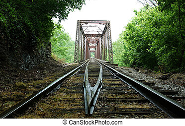 Train tracks leading to a bridge in the middle of nowhere