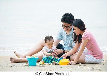 asian family enjoying quality time on the beach with father,...