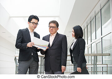 asian business team in a reporting meeting with office backgroun