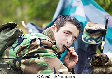 Young recruit with harmonica and rifle in forest