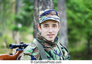 Young recruit with optical rifle in the woods